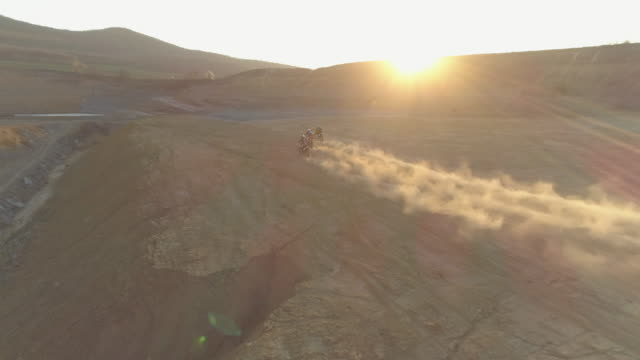 aerial drone view of men racing motocross motorcycles on a dirt off road at sunset. - slow motion - hungary stock videos & royalty-free footage