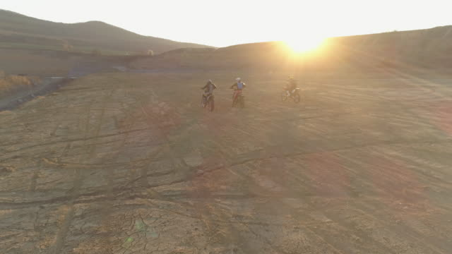 stockvideo's en b-roll-footage met aerial drone view of men racing motocross motorcycles on a dirt off road at sunset. - slow motion - men