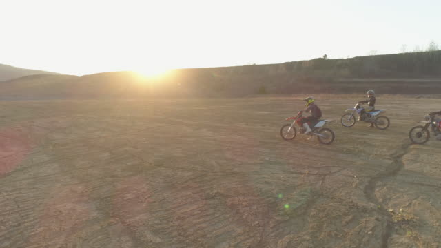 aerial drone view of men racing motocross motorcycles on a dirt off road at sunset. - slow motion - off road racing stock videos & royalty-free footage