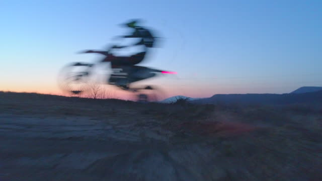 aerial drone view of men racing motocross motorcycles on a dirt off road at sunset. - slow motion - sports race stock videos and b-roll footage