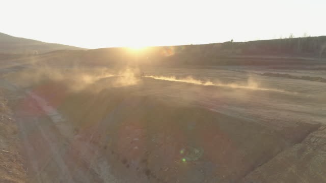 aerial drone view of men racing motocross motorcycles on a dirt off road at sunset. - slow motion - hard hat stock videos & royalty-free footage