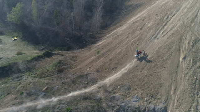 aerial drone view of men racing motocross motorcycles up hill. - slow motion - off road racing stock videos & royalty-free footage