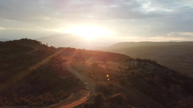 aerial drone view of men resting before riding motocross motorcycles at sunset on a dirt off road. - crash helmet stock videos & royalty-free footage