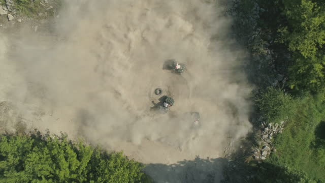 aerial drone view of men riding and racing atv quad motocross motorcycles vehicles in circles on a dirt off road. - slow motion - quadbike stock videos & royalty-free footage