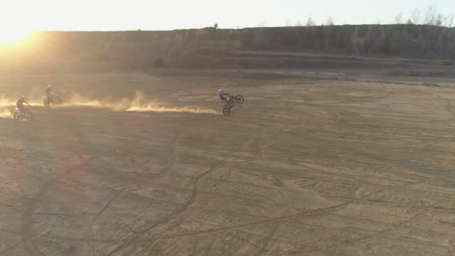 stockvideo's en b-roll-footage met aerial drone view of men riding motocross motorcycles and a man doing a wheelie trick. - men
