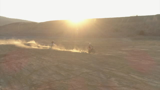 aerial drone view of men riding motocross motorcycles and a man doing a wheelie trick. - slow motion - dirt track stock videos & royalty-free footage