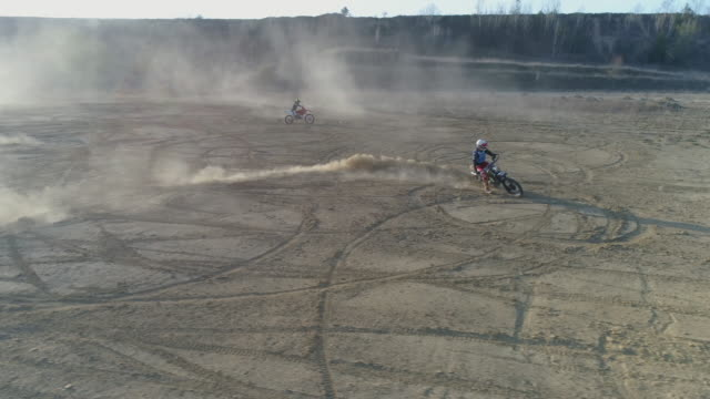Aerial drone view of men riding motocross motorcycles and making circles on a dirt off road. - Slow Motion
