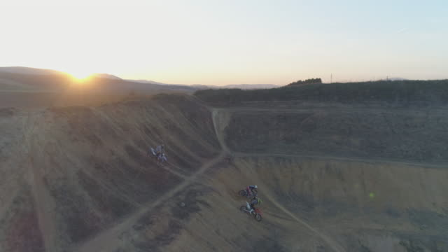 stockvideo's en b-roll-footage met aerial drone view of men riding motocross motorcycles up a hill at sunset. - men