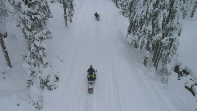 vídeos de stock e filmes b-roll de aerial drone view of men snowmobiling in the winter snow mountains. - slow motion - roménia