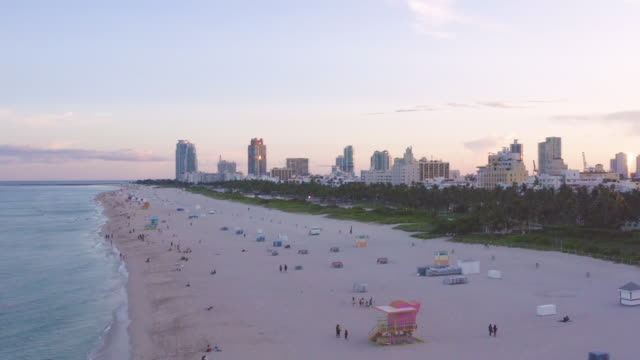 aerial drone view of miami south beach with lifeguard towers and waves on the beach, miami, florida at sunrise - アールデコ地区点の映像素材/bロール
