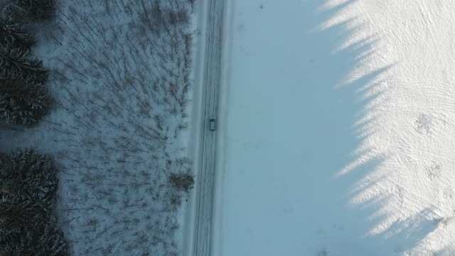 aerial drone view of minivan suv car driving on a snow covered forest and winter road trail. - sports utility vehicle stock videos & royalty-free footage