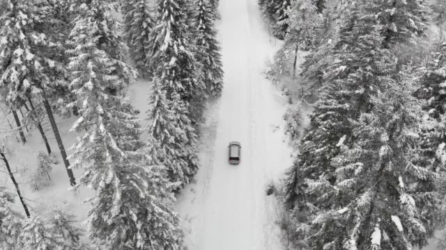 aerial drone view of minivan suv car driving on a snow covered forest and winter road trail. - snow stock videos & royalty-free footage
