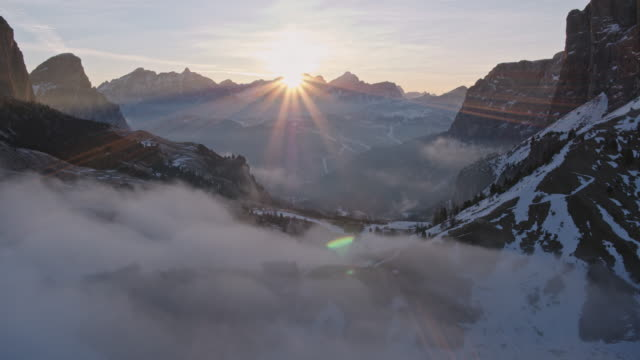 Aerial drone view of mist filled valley and mountains at sunrise