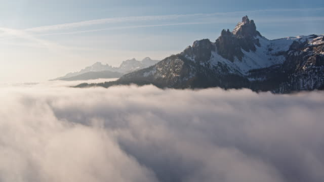 Aerial drone view of mist filled valley at sunrise in the mountains