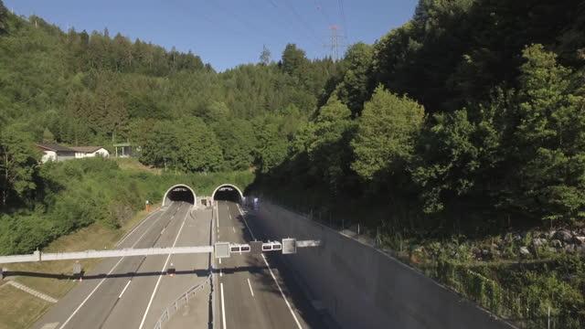 luft-drohnenansicht der autobahn, autos, die in den tunnel fahren - mehrspurige strecke stock-videos und b-roll-filmmaterial