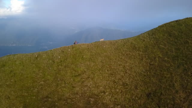 stockvideo's en b-roll-footage met luchtfoto drone weergave van mountainbiker oplopende ridge trail - stilstaand water