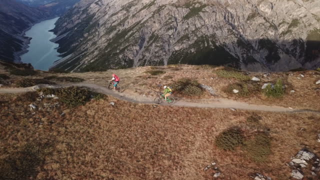 aerial drone view of mountain bikers riding mountain ridge - motorradfahrer stock-videos und b-roll-filmmaterial