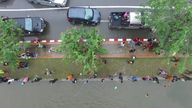 aerial drone view of people celebrating thai new year or songkran around the moat and city walls of chiang mai, thailand. new year is traditionally... - 水かけっこ点の映像素材/bロール