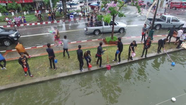 aerial drone view of people celebrating thai new year or songkran around the moat and city walls of chiang mai, thailand. new year is traditionally... - 水遊び点の映像素材/bロール