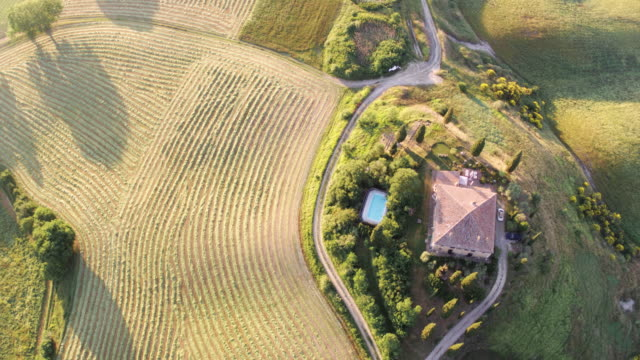Aerial drone view of rolling hills and farmhouse, Tuscany, Italy