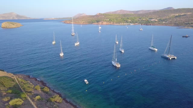 aerial drone view of sailboats anchored in a sheltered bay in greece. - anchored stock videos & royalty-free footage