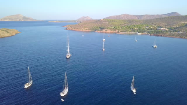 stockvideo's en b-roll-footage met aerial drone view of sailboats anchored in a sheltered bay in greece. - anchored