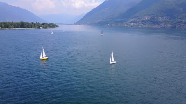 aerial drone view of sailboats sailing on lake maggiore, switzerland. - idylle stock-videos und b-roll-filmmaterial