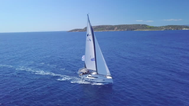 aerial drone view of sailing white sailboat near islands in greece and blue sea. - sailing boat stock videos & royalty-free footage