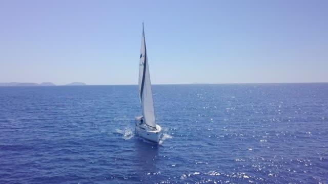 vídeos de stock e filmes b-roll de aerial drone view of sailing white sailboat near islands in greece and blue sea. - barco à vela