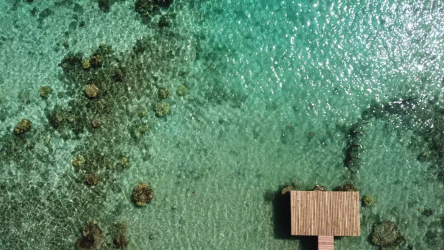 Aerial drone view of scenic sea and barrier reef in French Polynesia with a pontoon