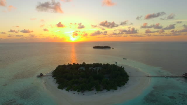 Aerial drone view of scenic tropical islands at sunset in the Maldives.