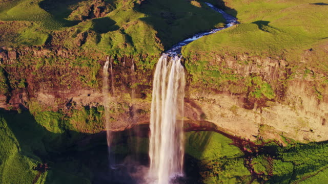 aerial drone view of seljalandsfoss waterfall at sunset, iceland - seljalandsfoss waterfall stock videos and b-roll footage