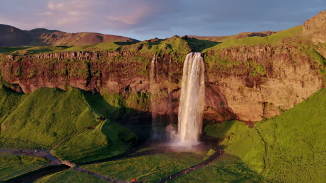 vídeos de stock, filmes e b-roll de aerial drone view of seljalandsfoss waterfall at sunset, iceland - cachoeira de seljalandsfoss