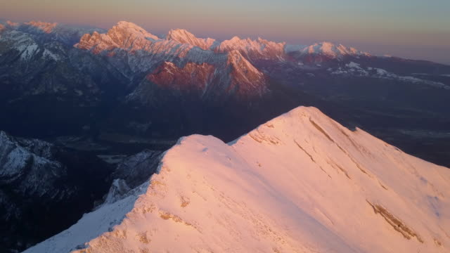 Aerial drone view of snow covered Alps mountains in the winter at sunset.
