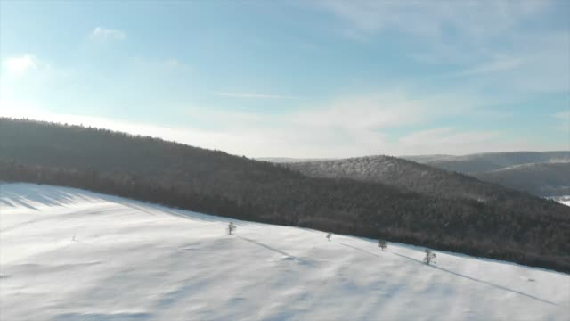 vidéos et rushes de aerial drone view of snow covered hill and trees. - pologne