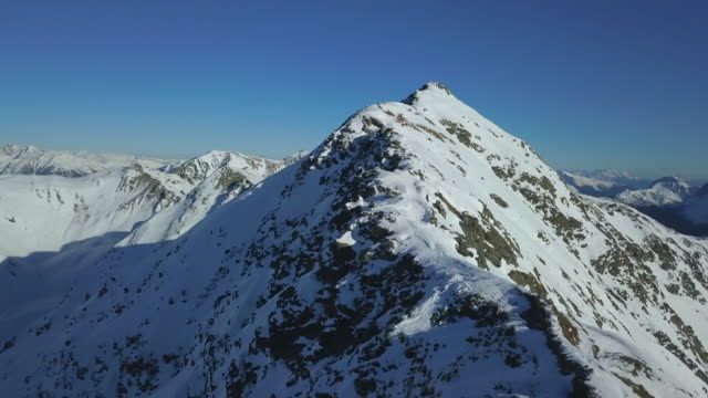 Aerial drone view of snow covered mountains in the winter.