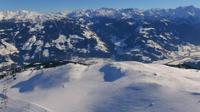 aerial drone view of snow mountains in winter at a ski resort. - austria stock videos & royalty-free footage