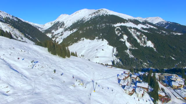 aerial drone view of snow mountains in winter at a ski resort. - stazione sciistica video stock e b–roll