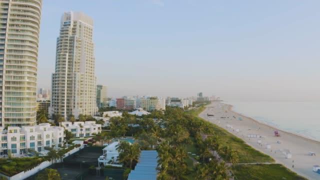 aerial drone view of south beach and skyscrapers, miami, florida at sunrise - オーシャンドライブ点の映像素材/bロール