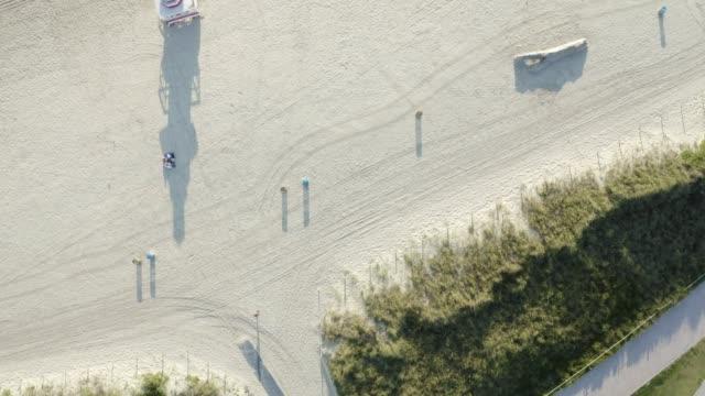 aerial drone view of south beach lifeguard tower and beach, miami, florida at sunrise - オーシャンドライブ点の映像素材/bロール