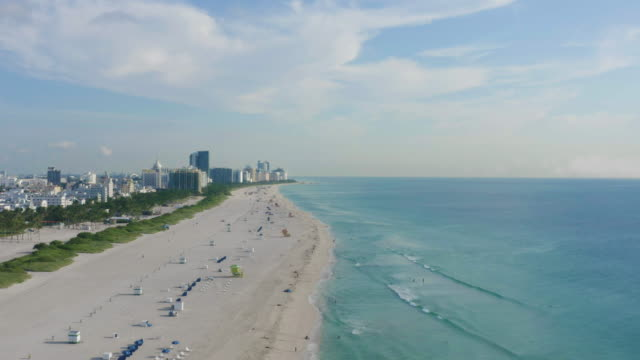 aerial drone view of south beach with lifeguard towers and waves on the beach, miami, florida at sunrise - アールデコ地区点の映像素材/bロール