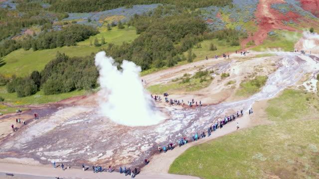 vídeos de stock, filmes e b-roll de aerial drone view of strokkur geyser erupting, geysir, iceland - gêiser strokkur