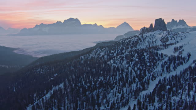 aerial drone view of sunrise over mist filled valley with mountain peaks - cortina stock videos & royalty-free footage