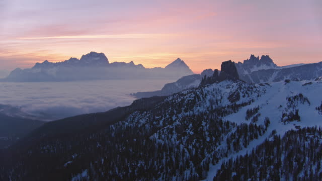 Aerial drone view of sunrise over mist filled valley with mountain peaks