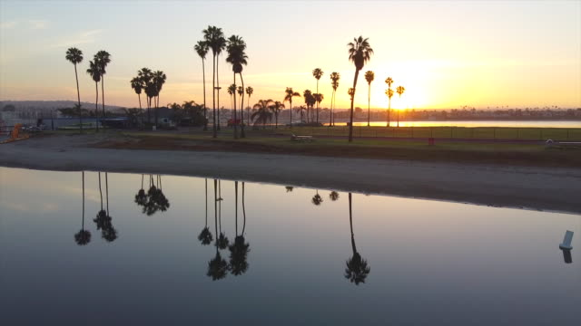 aerial drone view of sunrise reflection over calm mission bay, san diego, california. - time-lapse - san diego stock videos & royalty-free footage