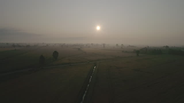 aerial drone view of sunset above green fields - empty road stock videos and b-roll footage