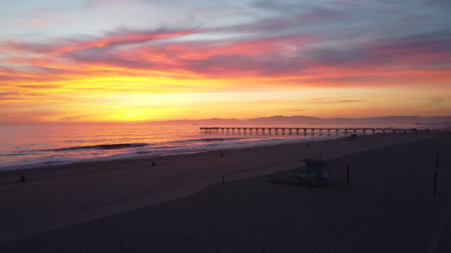 aerial drone view of sunset over a california pier, ocean and empty beach. - time-lapse - pier stock videos & royalty-free footage