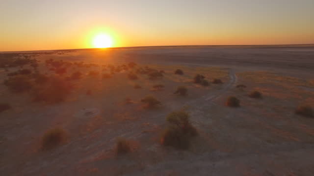 aerial drone view of sunset over a desert in africa plains. - plain stock videos & royalty-free footage