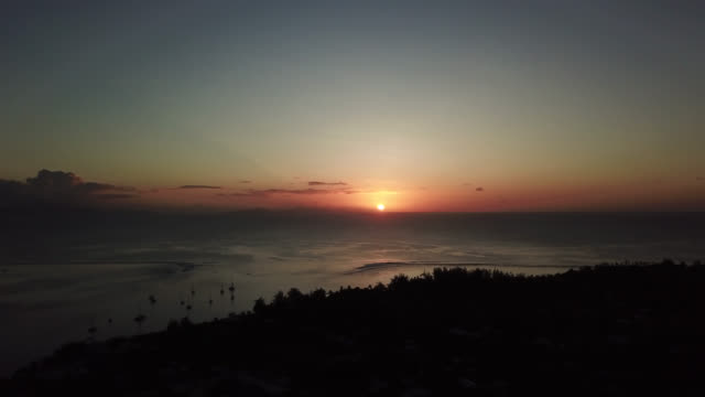 aerial drone view of sunset over the bay of fare, on the lagoon of the island of huahine - huahine island stock videos and b-roll footage