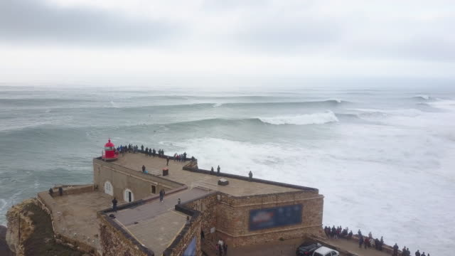 Aerial drone view of surfers surfing huge waves and the lighthouse at Nazare, Portugal.